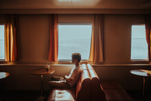 Young Man Travelling In Ferry On Rippling Sea