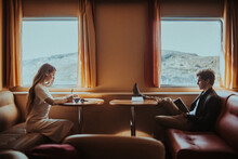 Focused Couple Reading Book And Writing Notes While Riding Ferry
