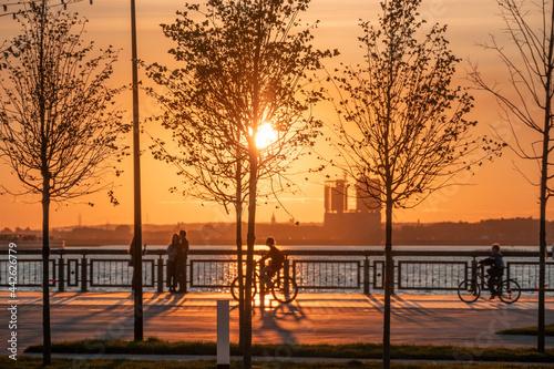 Fotografija Silhouettes of people walking along the embankment