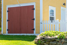 A Bright Yellow Shed With A Colorful Red Garage Door, White Trim, Windows, And A Small White Door. The Building Has A White Picket Fence Attached And Green Grass On The Ground Near The Structure.
