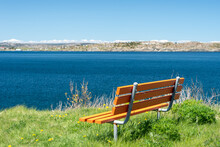 An Empty Orange Wooden Bench With Metal Posts On Long Lush Green Grass With Small Yellow Flowers. The Seat Has A Deep Blue Ocean In The Background With A Long Landmass And Blue Sky In The Background.