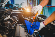 The Auto Mechanic In The Garage Is Checking The Engine And Oil For The Car That Is Being Serviced. Mechanic Working In Shop