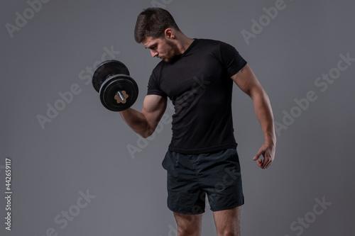 Sporty guy performing biceps curl with dumbbell Fotobehang