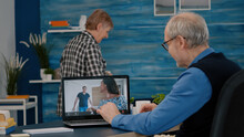 Happy Senior Man Waving During Video Conference With Nephews Using Laptop In Living Room. Elderly Person Using Internet Online Chat Technology Video Webcam Making Virtual Meeting Video Call