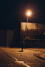 Person In Streetlight Rays Walking Along Street At Night In Suburb