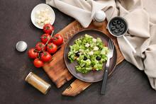 Wooden Plate With Fresh Greek Salad On Dark Background