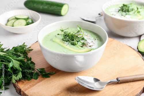 Bowls with green gazpacho and ingredients on light background
