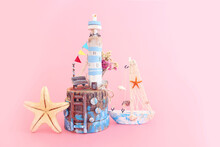 Nautical Concept With Sea Life Style Objects As Boat, Driftwood Beach House, Seashells And Starfish Over Pink Pastel Background