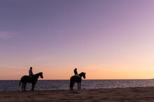 Unrecognizable Couple On Horses Admiring Sea From Beach At Sunset