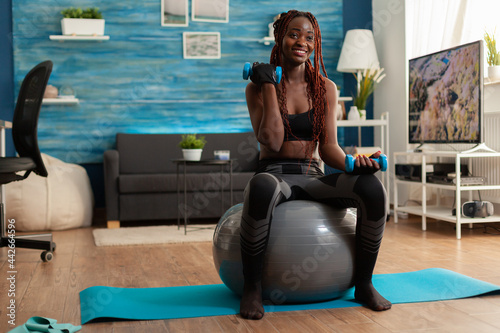 Canvas Joyful athletic black person in leggings using stability ball for training biceps, doing curls with dumbbells