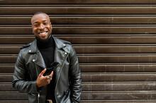 Cheerful Black Man Standing Against Brown Wall On Street