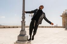 Cheerful Black Man Standing Near Street Lamp In City