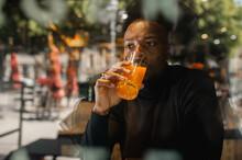 Black Man Drinking Juice In Cafe