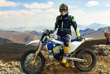 Man In Sport Equipment Riding A Motorcross Bike In Mountains