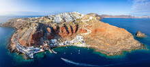 Panorama Of The Little Village Oia At The Edge Of The Volcanic Caldera On Santorini Island, Greece, With The Traditional Fishing Port Ammoudi Beneath