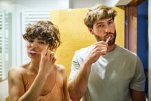 Couple Brushing Teeth In Bathroom Together