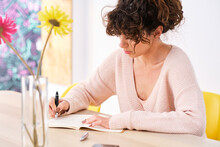 Thoughtful Woman Writing Notes In Copybook At Home
