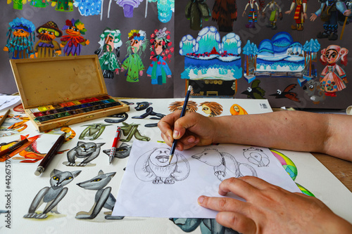 Photo The animator draws with a pencil and draws characters from cartoons, comics or puppet shows