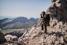 Military Man Speaking On Walkie Talkie In Mountains
