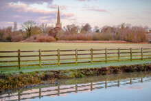 Countryside Landscape Of A River With A Fence With A Church Steeple In The Background Sunset Clouds On A White And Blue Sky With Reflections And A Tree Line And Copy Space
