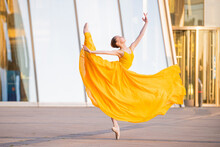 Young Ballerina In A Long Flying Yellow Dress Is Dancing Against The Backdrop Of Cityscape