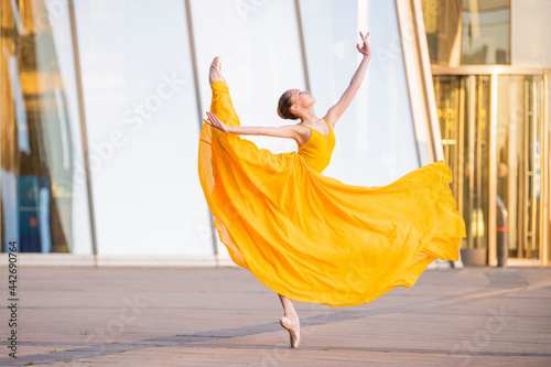 Leinwand Poster young ballerina in a long flying yellow dress is dancing against the backdrop of