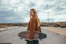 Serious Young Female Millennial With Skateboard In Hand Standing On Road