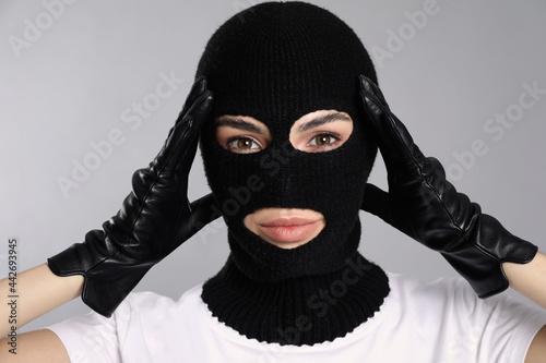 Woman wearing knitted balaclava on grey background Fototapeta