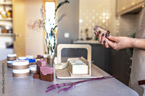 A soap-maker girl holds a piece of freshly brewed handmade soap in her hands Fotobehang