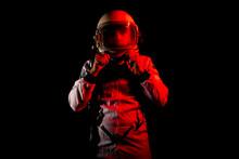 Astronaut In Space Suit Standing In Red Neon Light