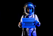 Serious Astronaut In Spacesuit Showing Placard With Warning Text