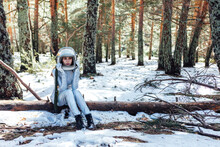 Determined Female In Space Helmet Sitting In Snowy Forest