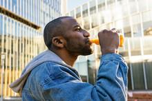 Black Man Drinking Delicious Beverage On City Street