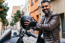 Smiling Ethnic Biker On Modern Motorcycle On City Street