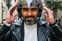 Smiling Hispanic Biker Putting On Helmet On Street