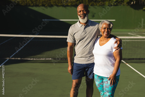 Portrait of smiling senior african american couple embracing on tennis court