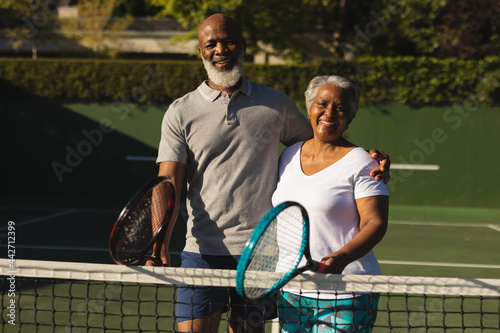 Portrait of smiling senior african american couple with tennis rackets on tennis court