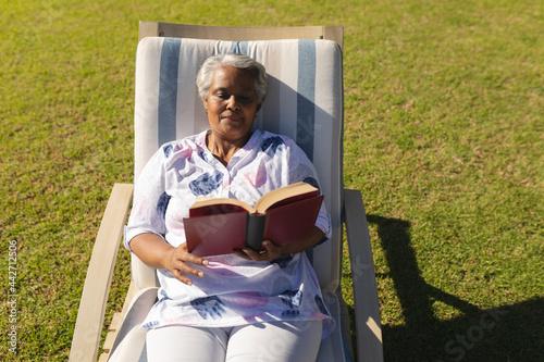 Senior african american woman reading book in deckchair in sunny garden