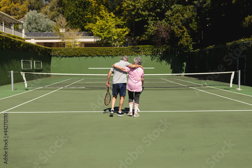 Senior caucasian couple embracing and walking on tennis court