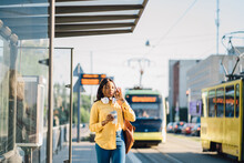 Attractive African American Female Traveler Or Student Waiting For Public Transport Standing On Bus Stop Outdoor At Sunny Morning With Transport On Blurred Background.