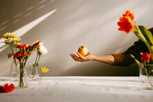 Person Throwing Apple In Studio With Flowers