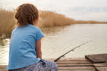Rear View. Little Girl Sits On A Wooden Bridge On A River With Fishing Rod.