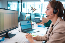 Caucasian Businesswoman Wearing Headset Talking And Using Computer With Colleagues In Background