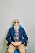 Senior Man In Eye Test Glasses In Clinic