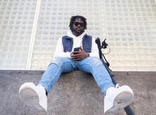 Stylish Black Man With Smartphone Resting On Urban Fence