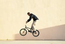 Black Athlete Riding BMX Bike On Platform