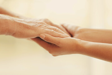 Helping hands on blurred background, closeup. Elderly care concept
