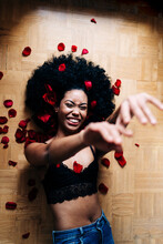 Happy Black Woman On Floor Covered Rose Petals