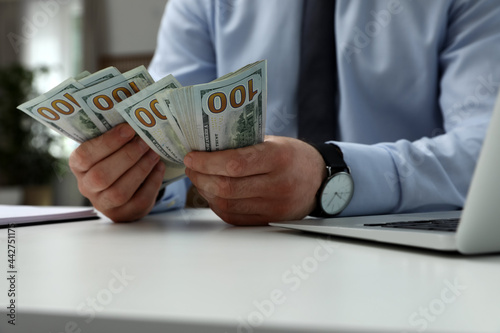 Photographie Cashier counting money at desk in bank, closeup