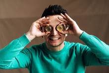 Smiling Trader Covering Eyes With Bitcoin Coins